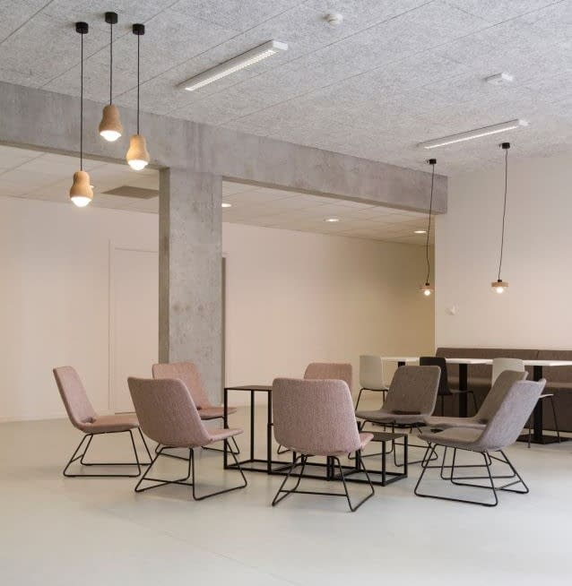 A group of beige chairs is centered in a plain-walled room with three lights hanging from the ceiling. Photo by Jean-Philippe Delberghe.